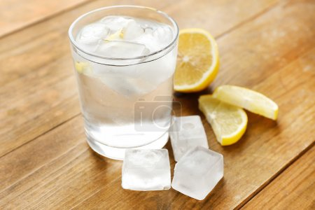 Glass of water with ice cubes on wooden table...