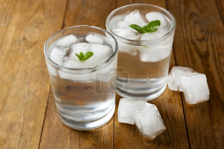 Glasses of water with ice cubes on wooden table...