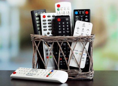 Photo pour De nombreux dispositifs de télécommande dans le panier sur fond clair - image libre de droit