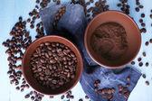 """Постер, картина, фотообои """"две миски молотого кофе и кофейных зерен на синем деревянном фоне с материалом джинсов"""""""