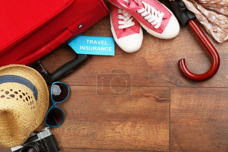 Photo for Suitcase and tourist stuff with inscription travel insurance on wooden background - Royalty Free Image