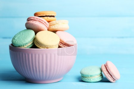 Photo for Assortment of gentle colorful macaroons in colorful bowl on color wooden background - Royalty Free Image