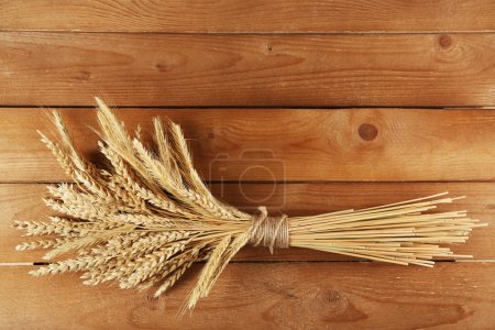 Spikelets of wheat on wood