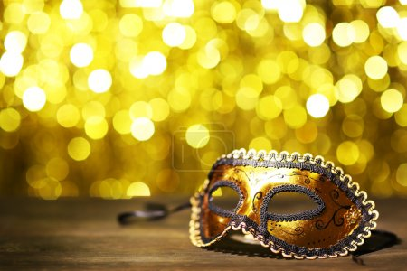 Photo pour Beautiful carnival mask on table on golden background - image libre de droit