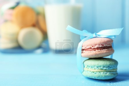 Photo for Gentle colorful macaroons in glass jars, milk glass and towel on color wooden table background - Royalty Free Image