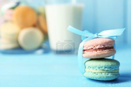 Foto de Gentle colorful macaroons in glass jars, milk glass and towel on color wooden table background - Imagen libre de derechos