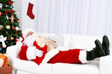Photo for Santa Claus sleeping at home near Christmas tree - Royalty Free Image