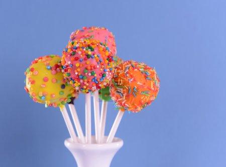 Sweet cake pops in vase on blue background