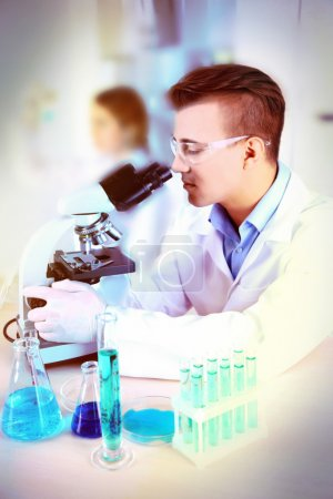 Young male researcher carrying out scientific research in lab