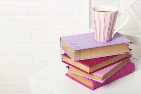 Photo for Pile of books with cup on the chair on brick wall background - Royalty Free Image