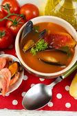 """Постер, картина, фотообои """"вкусный суп с креветками, мидиями, помидорами и черными маслинами в миске на деревянном фоне"""""""