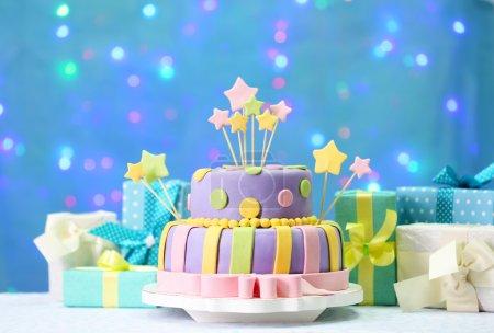 Photo for Delicious birthday cake on shiny blue background - Royalty Free Image