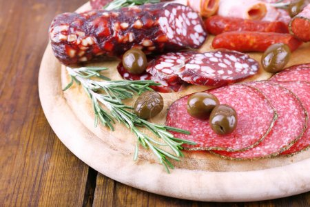 Assortment of sausages on cutting board and wooden...