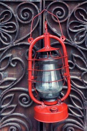 Kerosene lamp on wrought iron gates background