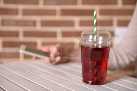 Pomegranate juice in fast food closed cup with tube on wooden table and female hand on brick wall background