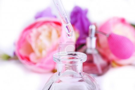 Photo for Dropper bottle of perfume with flowers on light background - Royalty Free Image