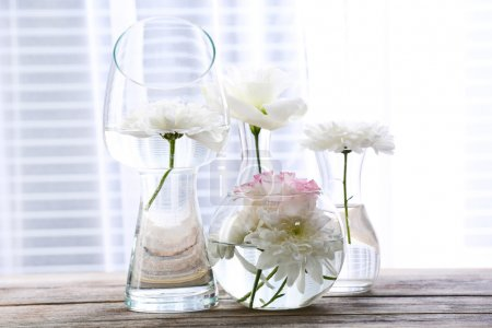 Beautiful flowers in vases with light from window