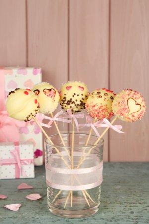 Photo pour Délicieux gâteau pop et des cadeaux sur fond en bois - image libre de droit