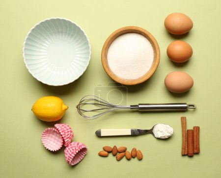 Photo for Food ingredients and kitchen utensils for cooking on green background - Royalty Free Image