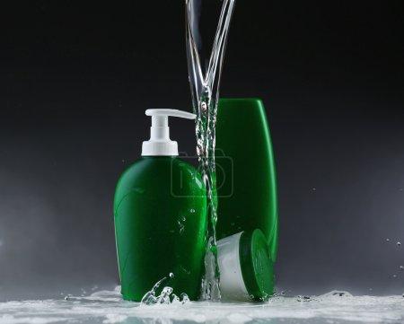 Photo pour Produits cosmétiques dans les éclaboussures d'eau sur fond gris - image libre de droit