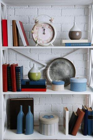 Photo pour Étagères avec des livres et des objets décoratifs sur fond de mur de brique - image libre de droit