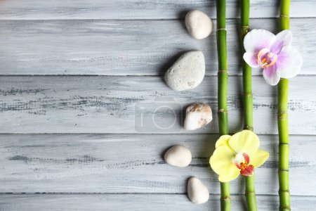 Photo for Orchid flowers  and bamboo with pile stones on wooden background - Royalty Free Image