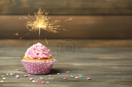 Cupcake with sparkler on table on wooden backgroun...