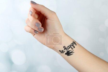 Photo pour Bras féminin avec tatouage sur fond clair - image libre de droit