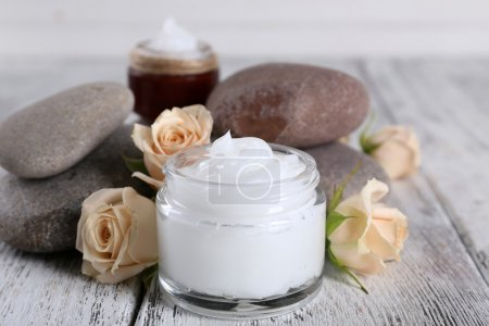 Photo for Cosmetic cream with flowers and spa stones on wooden background - Royalty Free Image