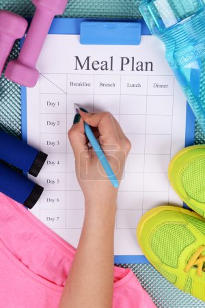 Photo for Sports trainer amounts to meal plan and sports equipment top view close-up - Royalty Free Image