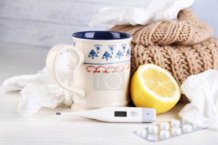 Photo for Hot tea for colds, pills and handkerchiefs on table close-up - Royalty Free Image
