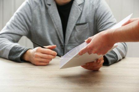 Photo pour Auteur, signant des autographes au dossier propre à la table en bois sur fond blanc planches - image libre de droit