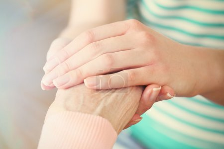 Old and young holding hands on light background, c...
