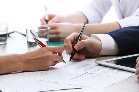 Photo pour Réunion à la table de travail sur fond blanc flou - image libre de droit