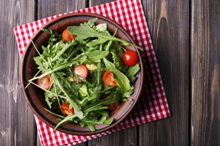 Salad with arugula and cherry tomatoes on wooden table