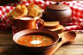 Ukrainian beetroot soup - borscht in bowl and pot, on napkin, on wooden background