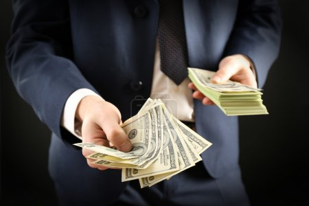 Photo for Businessman giving money on dark background - Royalty Free Image