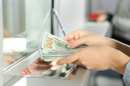 Female hand with money in cash department window. ...
