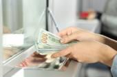 Weiblichen Hand mit Geld in Bargeld Abteilung Fenster. Konzept der Währung-Austausch