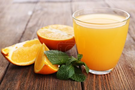Glass of orange juice with oranges on wooden table close up