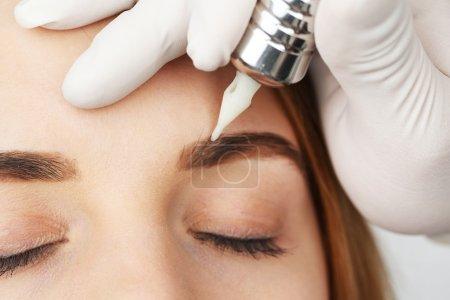 Photo pour Cosmetologue faisant du maquillage permanent, gros plan - image libre de droit