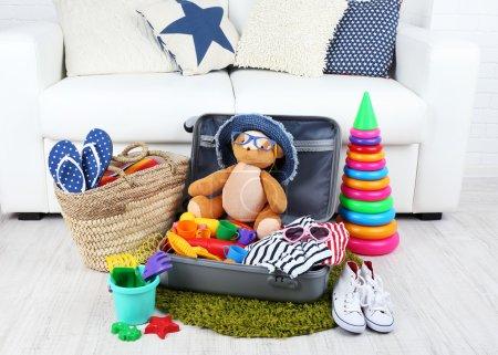 Photo pour Valise remplie de vêtements et de jouets pour enfants sur tapis en fourrure et fond de canapé blanc - image libre de droit