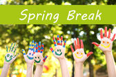 Spring break concept. Smiling colorful hands on nature background