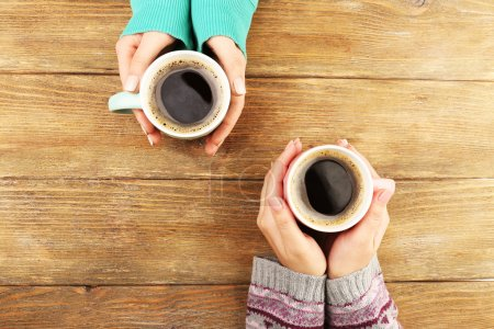 Photo for Female hands holding cups of coffee on rustic wooden table background - Royalty Free Image