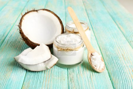Fresh coconut oil in glassware and wooden spoon on color wooden table background