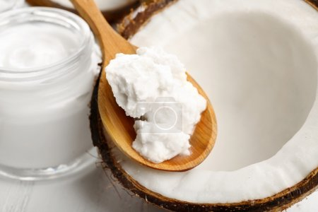 Coconut with coconut oil and jar of cosmetic cream on table close up