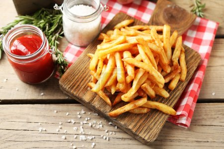 Photo for Tasty french fries on cutting board, on wooden table background - Royalty Free Image