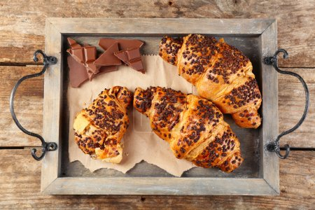 Photo for Fresh and tasty croissants with chocolate on wooden tray, on wooden background - Royalty Free Image
