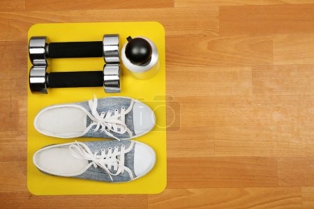 Shoes and sports equipment on mat on wooden floor,...