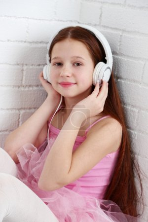 Beautiful little ballerina with headphones on  white bricks wall background